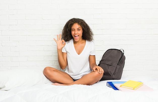 Młody afroamerykanin student kobieta łóżko mruga okiem i trzyma w porządku gest ręką.
