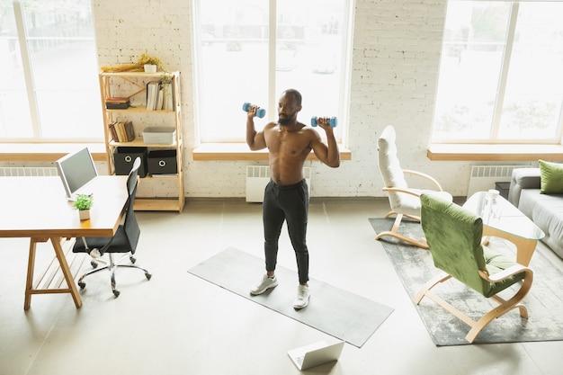 Młody afroamerykanin trenujący w domu podczas kwarantanny z powodu epidemii koronawirusa ćwiczenia doinc