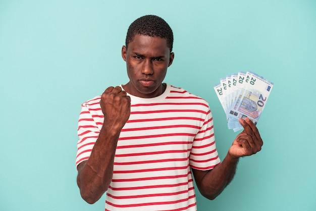 Młody afroamerykanin trzyma banknoty na białym tle na niebieskim tle pokazując pięść do kamery, agresywny wyraz twarzy.