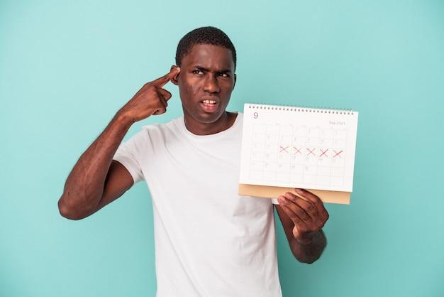 Młody afroamerykanin trzyma kalendarz na białym tle na niebieskim tle pokazujący gest rozczarowania palcem wskazującym.
