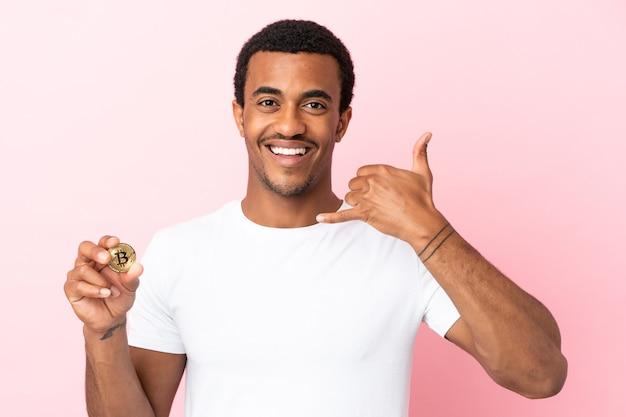 Młody afroamerykanin, trzymając bitcoin na na białym tle różowy, co telefon gest. oddzwoń do mnie znak