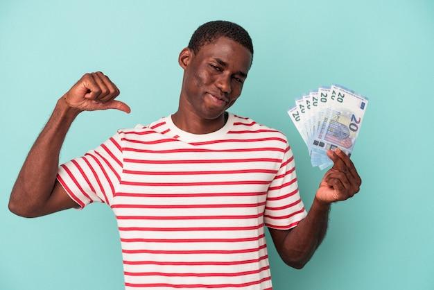 Młody afroamerykanin trzymający banknoty na białym tle na niebieskim tle czuje się dumny i pewny siebie, przykład do naśladowania.