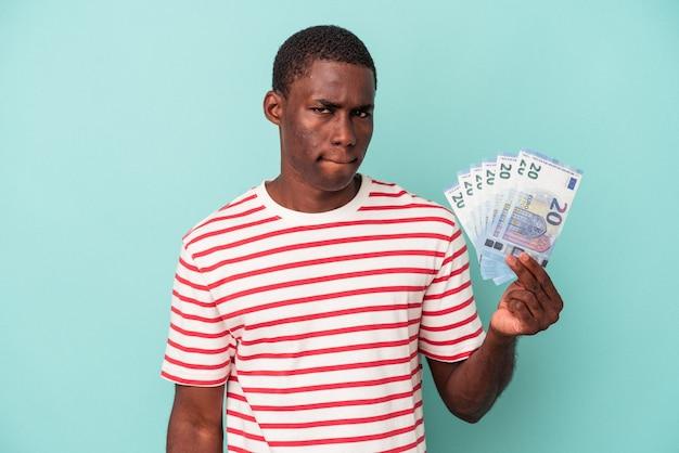Młody afroamerykanin trzymający banknoty na białym tle na niebieskim tle zdezorientowany, czuje się niepewny i niepewny.