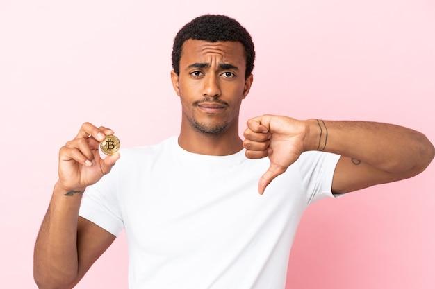 Młody afroamerykanin trzymający bitcoina na białym tle, pokazując kciuk w dół z negatywnym wyrazem twarzy