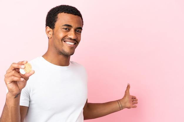 Młody afroamerykanin trzymający bitcoina na różowym tle, wyciągając ręce do boku, zapraszając do siebie