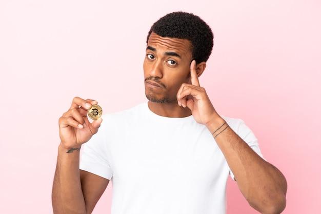 Młody afroamerykanin trzymający bitcoina nad odosobnionym różowym tłem, myślący o pomyśle