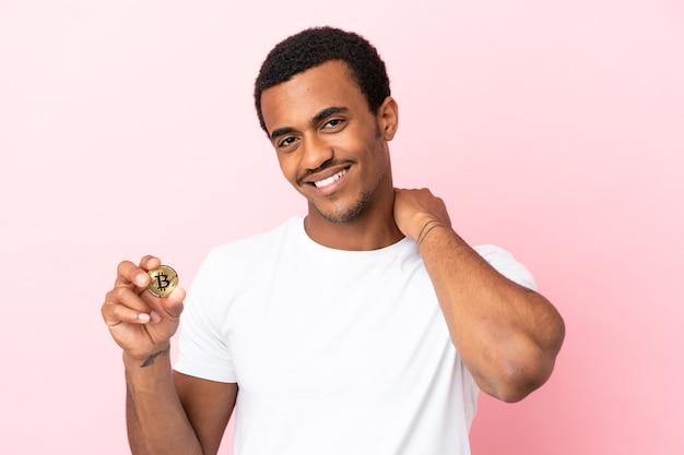 Młody afroamerykanin trzymający bitcoina nad odosobnionym różowym tłem, śmiejąc się