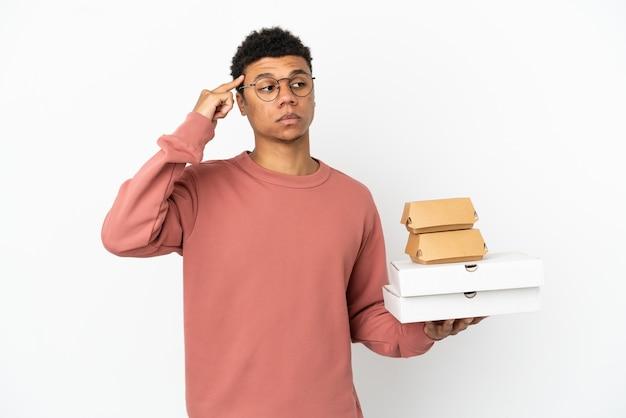 Młody afroamerykanin trzymający burgera i pizze na białym tle mający wątpliwości i myślący