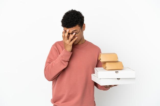 Młody afroamerykanin trzymający burgera i pizze na białym tle ze zmęczonym i chorym wyrazem