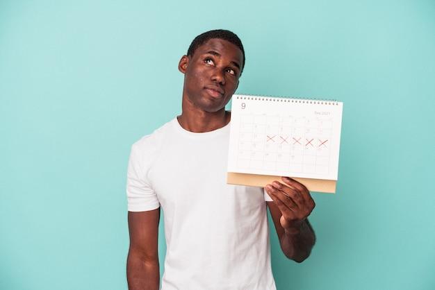 Młody afroamerykanin trzymający kalendarz na białym tle na niebieskim tle, marzący o osiągnięciu celów i celów