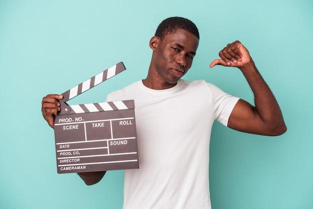 Młody afroamerykanin trzymający klaps na białym tle na niebieskim tle czuje się dumny i pewny siebie, przykład do naśladowania.