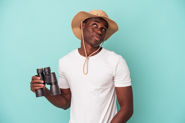 Młody afroamerykanin trzymający lornetkę na białym tle na niebieskim tle, marzący o osiągnięciu celów i celów