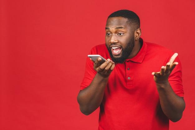 Młody afroamerykanin używający smartfona zestresowany, zszokowany wstydem i zaskoczeniem na twarzy, zły i sfrustrowany
