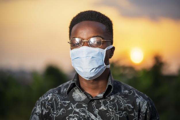 Młody afroamerykanin w ochronnej masce na twarz pozuje na zewnątrz