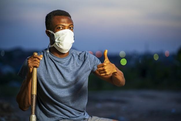 Młody afroamerykanin w ochronnej masce na twarz, trzymający łopatę i gestykulujący kciukiem w górę