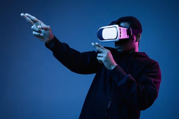 Młody afroamerykanin w okularach vr w neonowym kolorze niebieskim