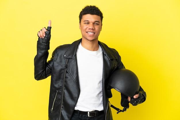 Młody afroamerykanin z kaskiem motocyklowym na białym tle na żółtym tle wskazujący świetny pomysł
