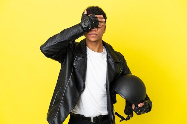 Młody afroamerykanin z kaskiem motocyklowym na białym tle na żółtym tle zasłaniając oczy rękami. nie chcę czegoś widzieć