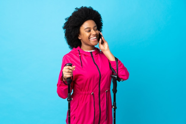 Młody afroamerykanin z plecakiem i kijkami na niebieskiej ścianie, prowadzący rozmowę z telefonem komórkowym