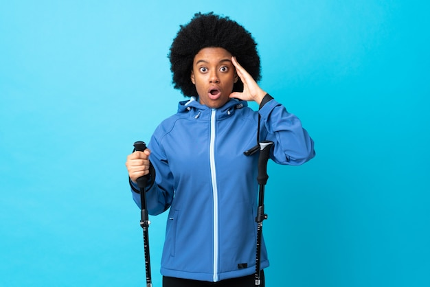 Młody afroamerykanin z plecakiem i kijkami trekkingowymi izolowanymi na niebieskiej ścianie zdał sobie sprawę z czegoś i zamierza rozwiązać problem