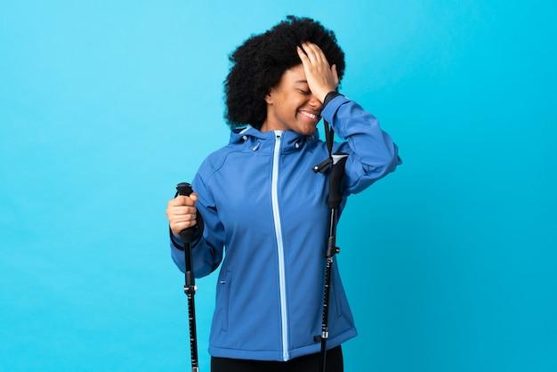 Młody afroamerykanin z plecakiem i kijkami trekkingowymi na niebieskiej ścianie coś sobie uświadomił i zamierza rozwiązać problem