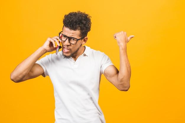Młody afroamerykanin za pomocą smartfona zestresowany, zszokowany wstydem i zaskoczeniem twarzy