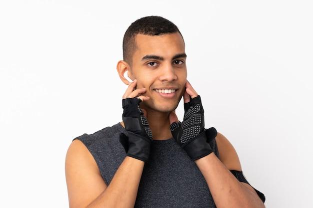 Młody afroamerykanów człowiek sportu na białym tle słuchanie muzyki na białej ścianie