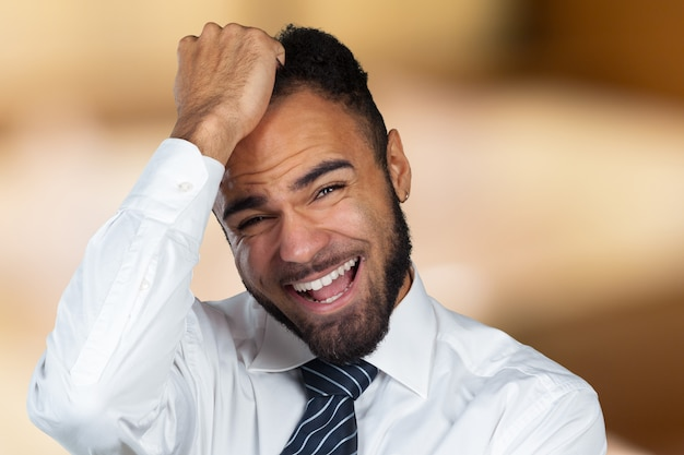 Młody afroamerykański biznesmen cierpi na ból głowy po ciężkim dniu pracy