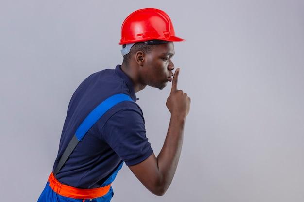 Młody afroamerykański budowniczy mężczyzna ubrany w mundur konstrukcyjny i kask ochronny stojący bokiem, prosząc o ciszę z palcem na ustach ciszę i tajną koncepcję