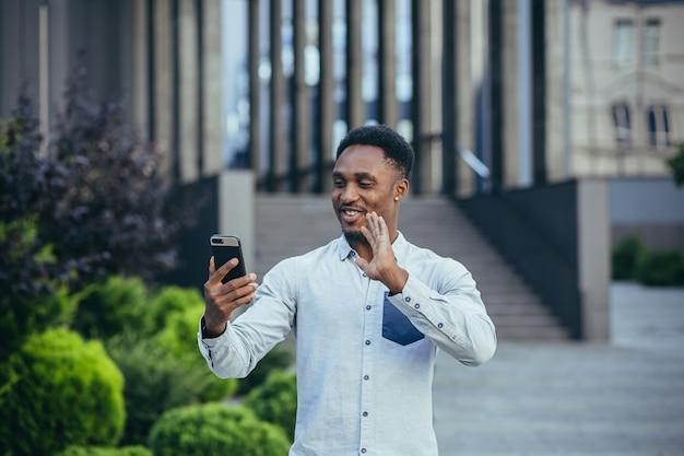 Młody afroamerykański freelancer rozmawiający podczas rozmowy wideo w pobliżu biura wesoły uśmiechnięty mężczyzna