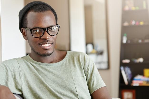 Młody afroamerykański freelancer w kapeluszu i prostokątnych okularach czuje się szczęśliwy i zrelaksowany po zakończeniu pracy, siedząc w swoim przytulnym pokoju. murzyn odpoczywa w domu