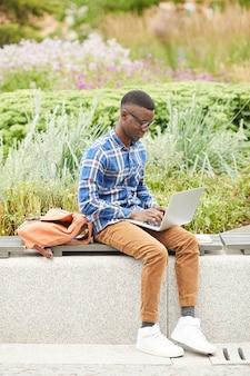 Młody afroamerykański mężczyzna używa laptop outdoors