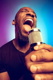 Młody afroamerykański muzyk jazzowy śpiewa piosenkę na gradiencie fioletowo-niebieskim