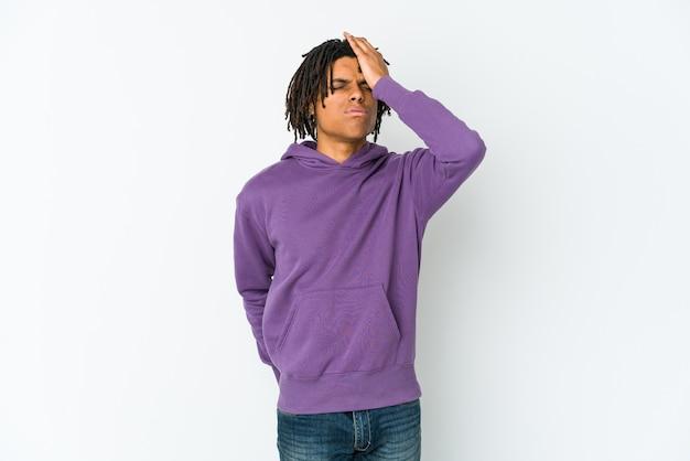 Młody afroamerykański rastaman zapomina o czymś, klepie dłonią w czoło i zamyka oczy.