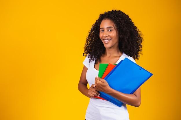 Młody afroamerykański student na żółtym tle