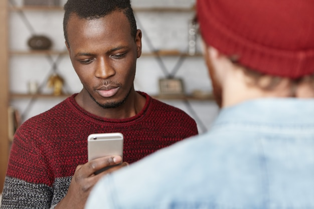 Młody afroamerykański student trzymający telefon komórkowy, piszący wiadomości podczas rozmowy ze swoim nierozpoznawalnym stylowym kaukaskim przyjacielem w kawiarni