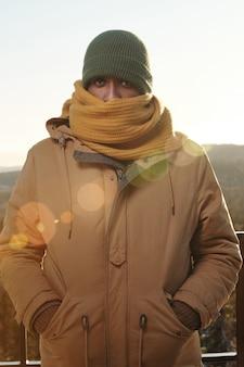 Młody afrykanin w ciepłym wełnianym szaliku zakrywającym dolną część jego twarzy i odzieży zimowej czuje zimno w mroźny zimowy dzień na tle jasnego nieba