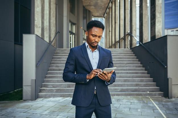 Młody afrykański biznesmen czyta wiadomości z tabletu, ubrany w garnitur w pobliżu biura