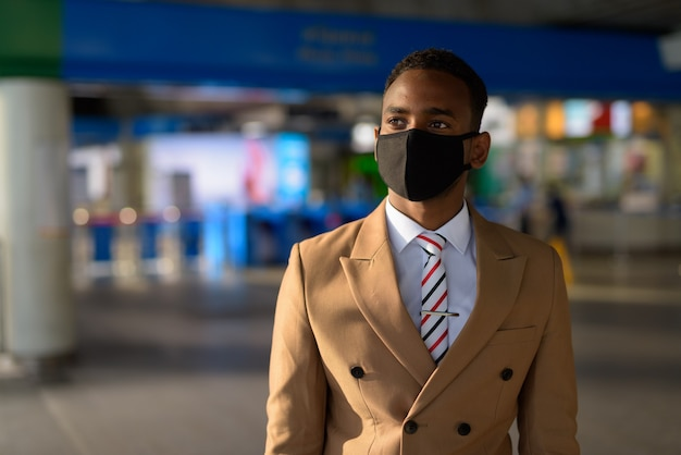 Młody afrykański biznesmen myśli z maską do ochrony przed wybuchem koronawirusa na dworcu nieba