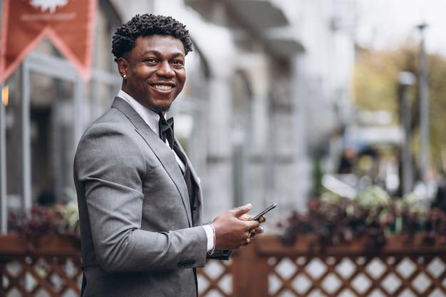 Młody afrykański biznesmen używa telefon