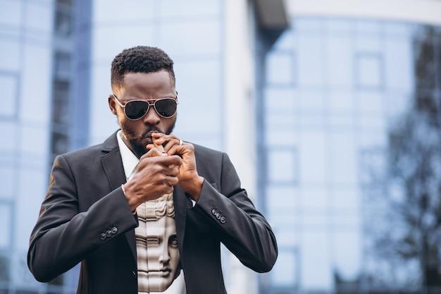 Młody afrykański biznesmen w klasycznym garniturze palenia papierosów