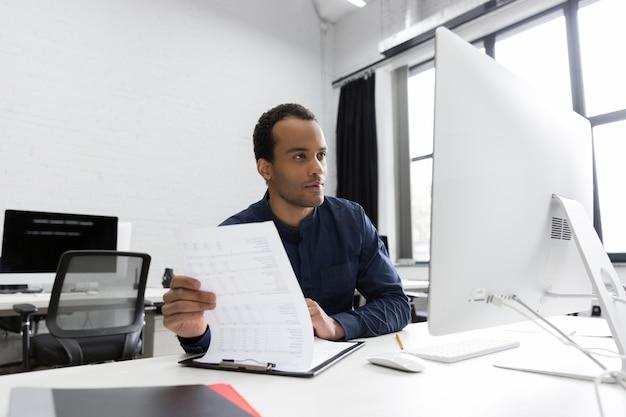 Młody afrykański biznesowego mężczyzna obsiadanie przy jego biurkiem