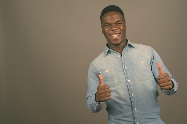 Młody afrykański człowiek ubrany w dżinsową koszulę