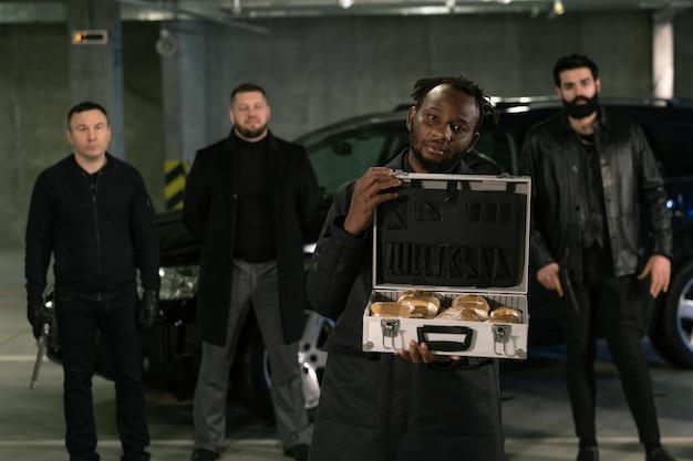 Młody afrykański gangster lub dealer narkotyków, trzymając otwartą walizkę pełną narkotyków ze swoim uzbrojonym gangiem na tle