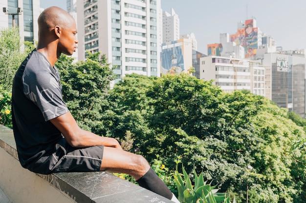 Młody afrykański męski atleta siedzi na krawędzi dachu z widokiem na miasto