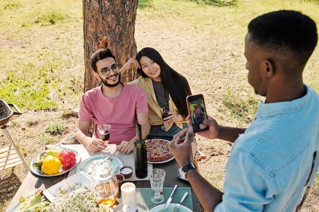Młody afrykański mężczyzna fotografuje międzykulturową parę ze smartfonem siedząc pod sosną przed stołem serwowanym na kolację