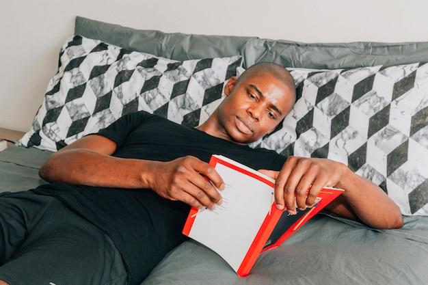 Młody afrykański mężczyzna kłama na łóżkowej czytelniczej książce