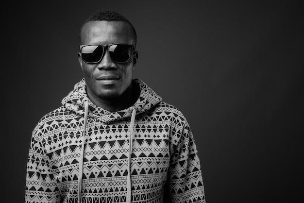 Młody afrykański mężczyzna nosi bluzę z kapturem i okulary przeciw szarej ścianie. czarny i biały