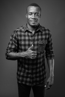 Młody afrykański mężczyzna nosi koszulę w kratkę przed szarej ścianie. czarny i biały