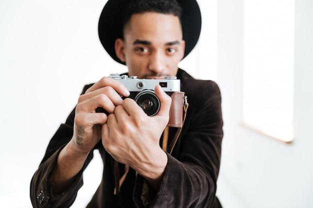 Młody afrykański mężczyzna robi fotografii na retro kamerze